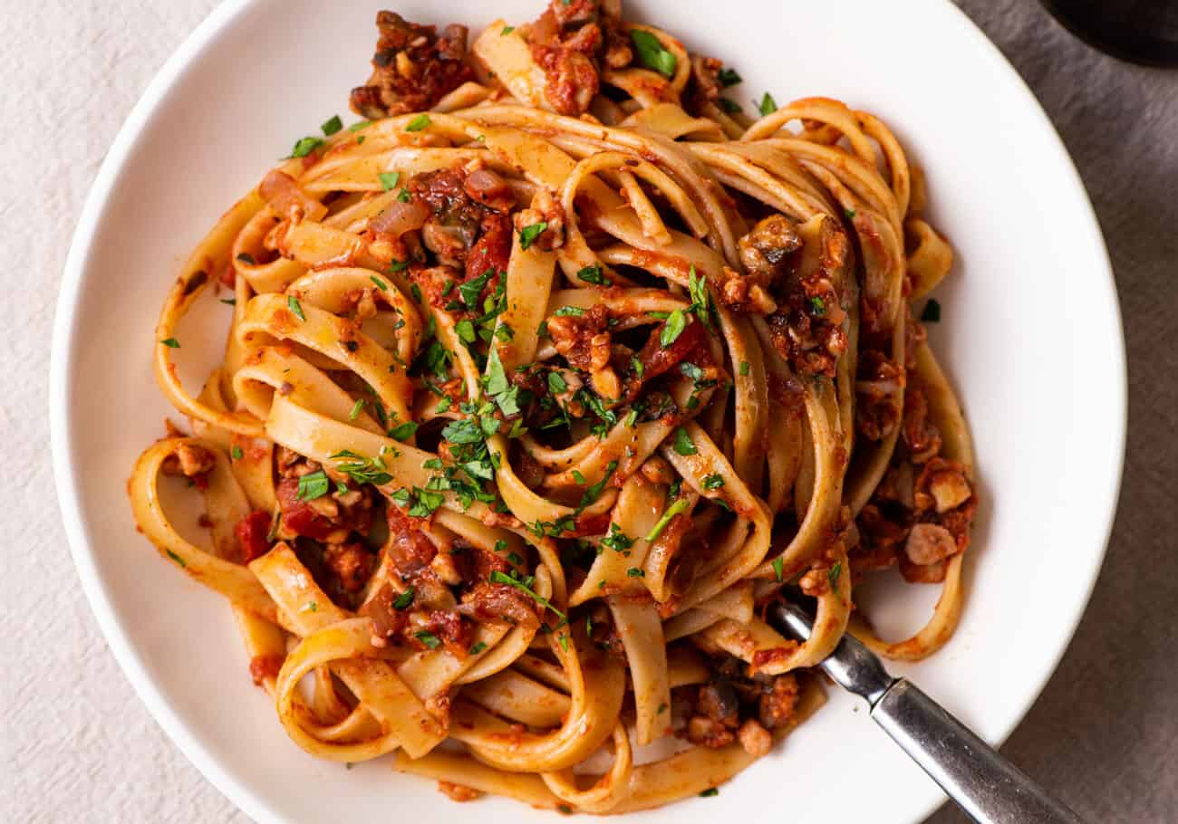 Fettuccine with tempeh bolognese in a white bowl.