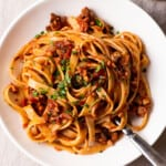 Tempeh Bolognese over spaghetti on a white plate on a wooden table