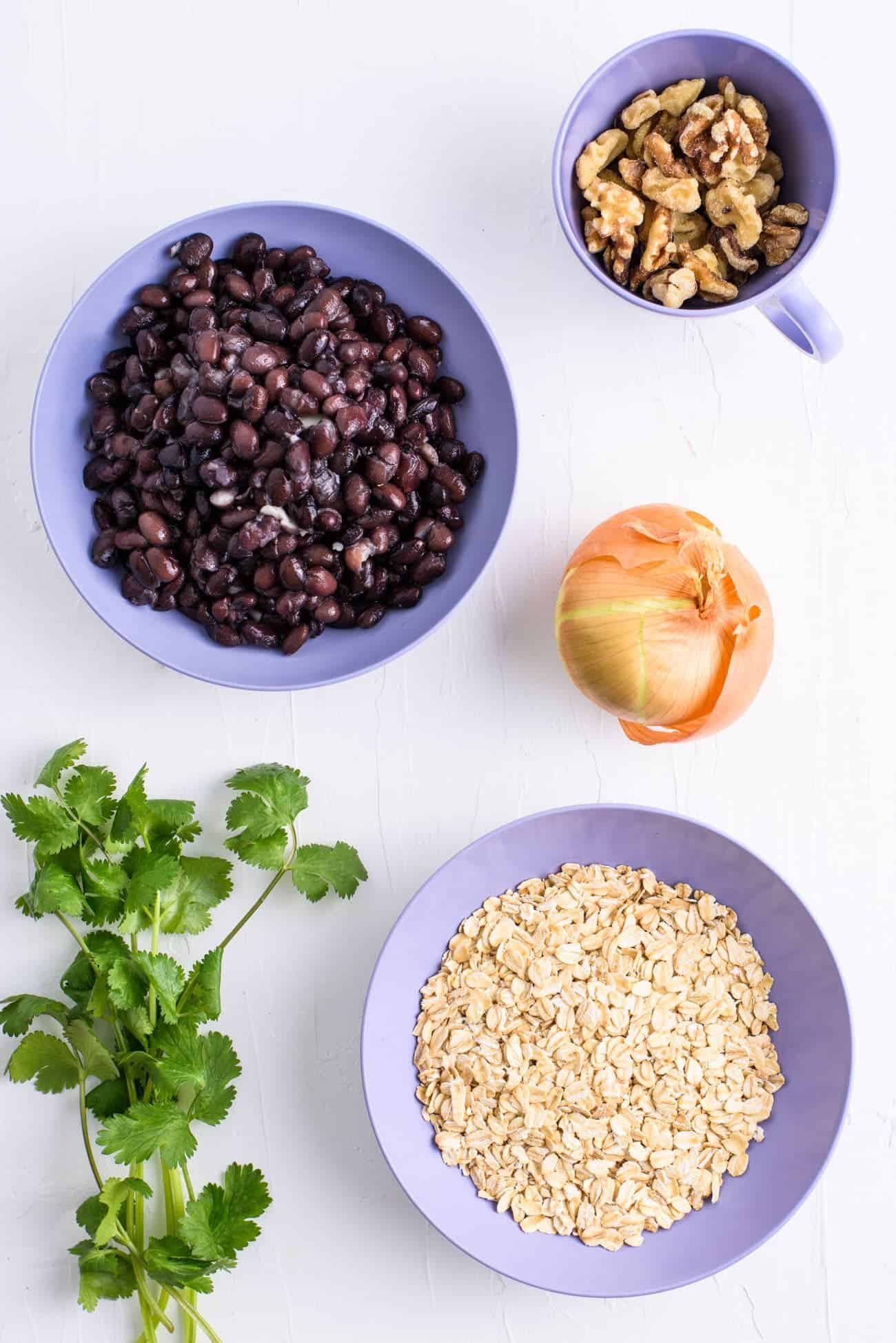 Ingredients to make vegan gluten-free black bean burgers laid out on a while table