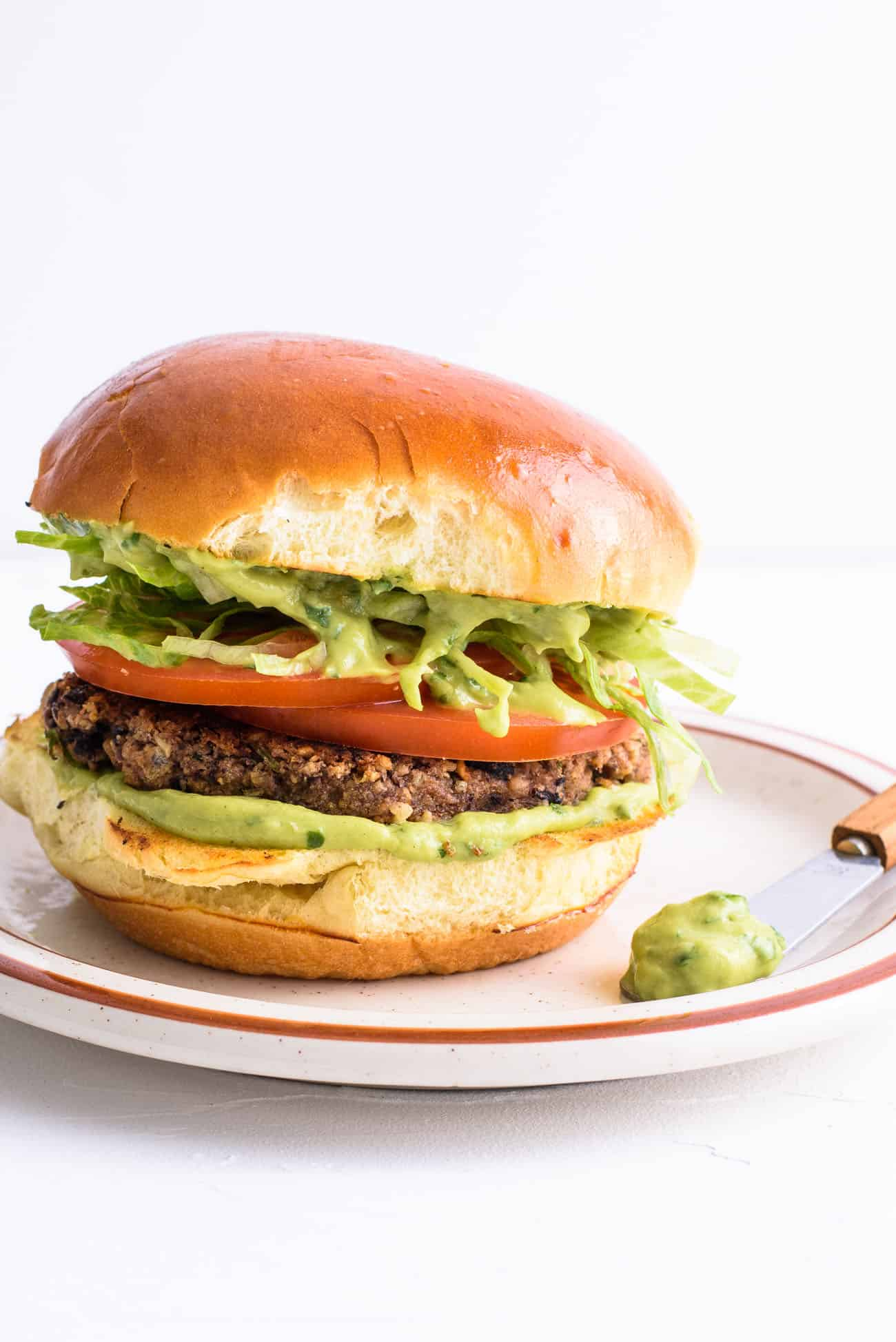 Close-up on vegan black bean burger on a toasted brioche bun with guacamole, lettuce and tomatoes