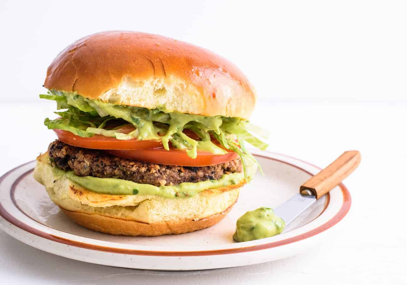 Close-up of vegan gluten-free black bean burger on a toasted brioche bun with guacamole, lettuce and tomatoes
