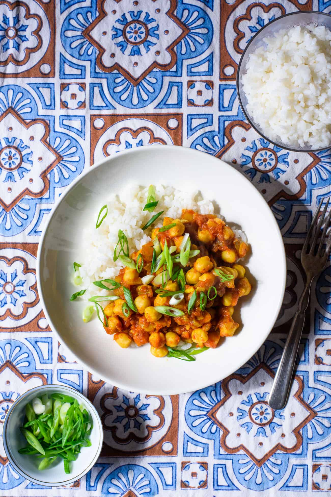 Bowl of chana masala on an Indian-patterned tablecloth next to rice and scallions