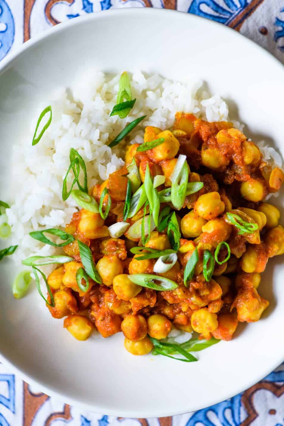 Close-up photo of bowl of chana masala with rice and scallions | Easy chana masala recipe