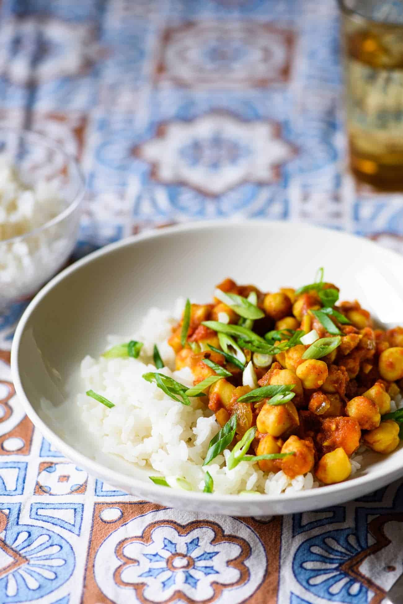 Bowl of chana masala on an Indian-patterned tablecloth