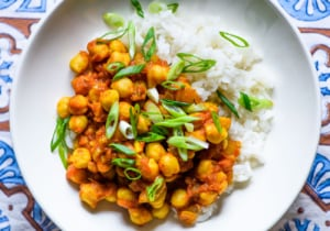 Close-up photo of bowl of chana masala with rice and scallions