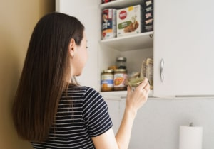 Woman reaching into cupboard