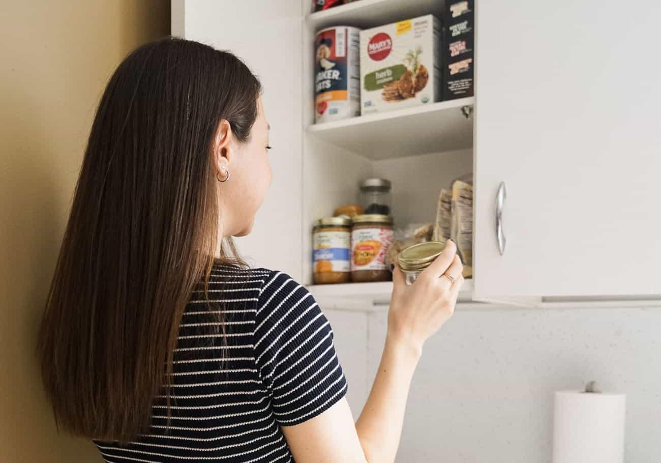Woman reaching into cupboard