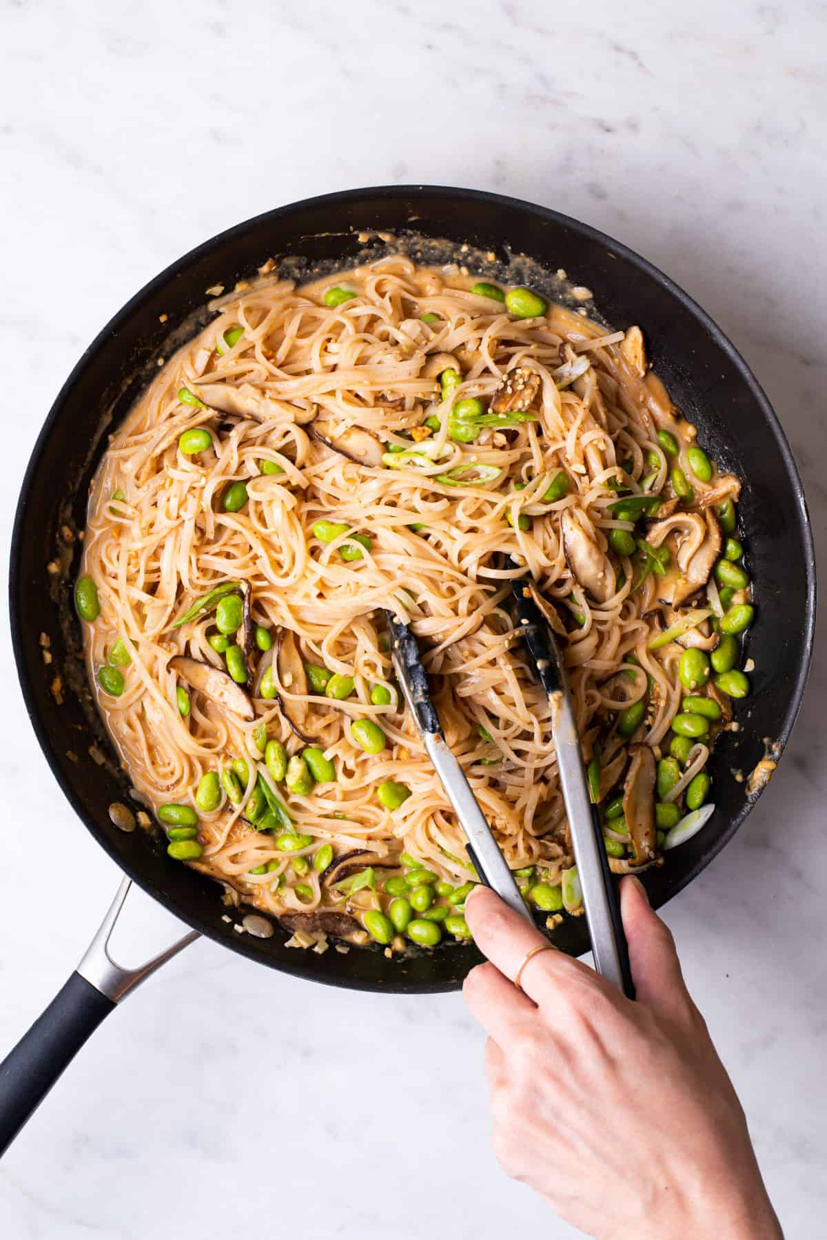 Woman's hand tossing creamy peanut noodles in a skillet with tongs.