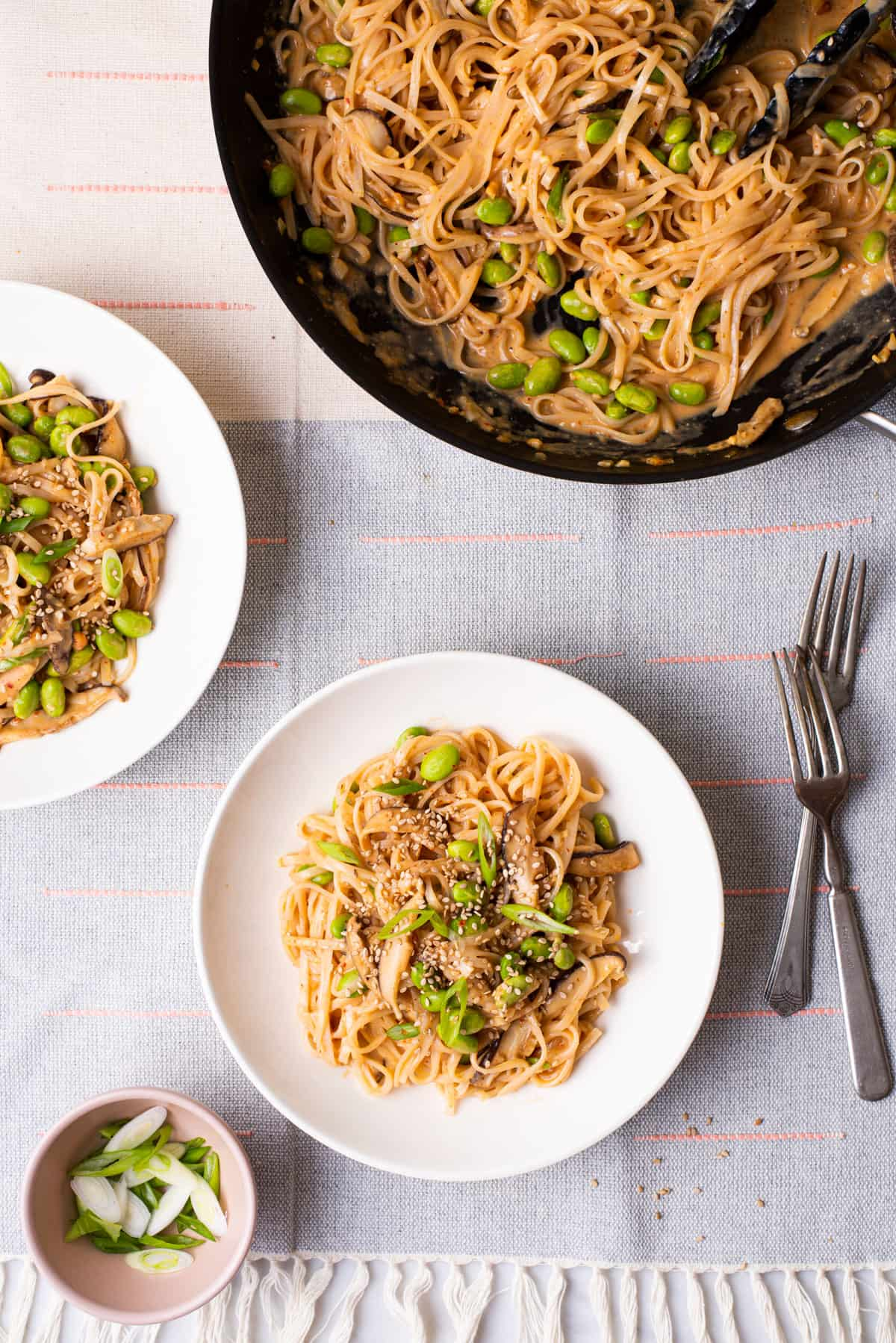 Peanut miso noodles in a skillet next to 2 bowls on a linen tablecloth.