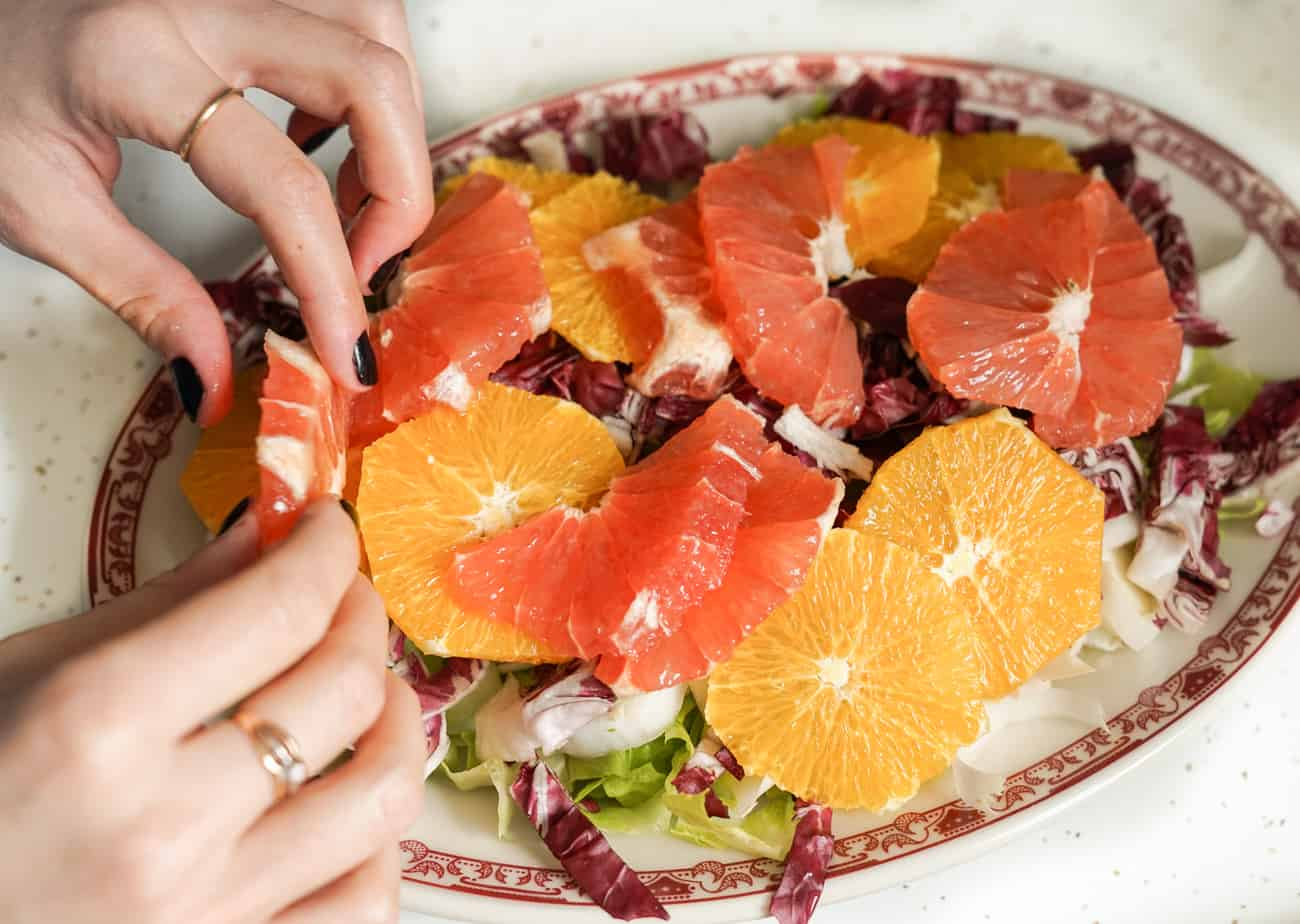 Woman's hands assembling chicories salad with citrus