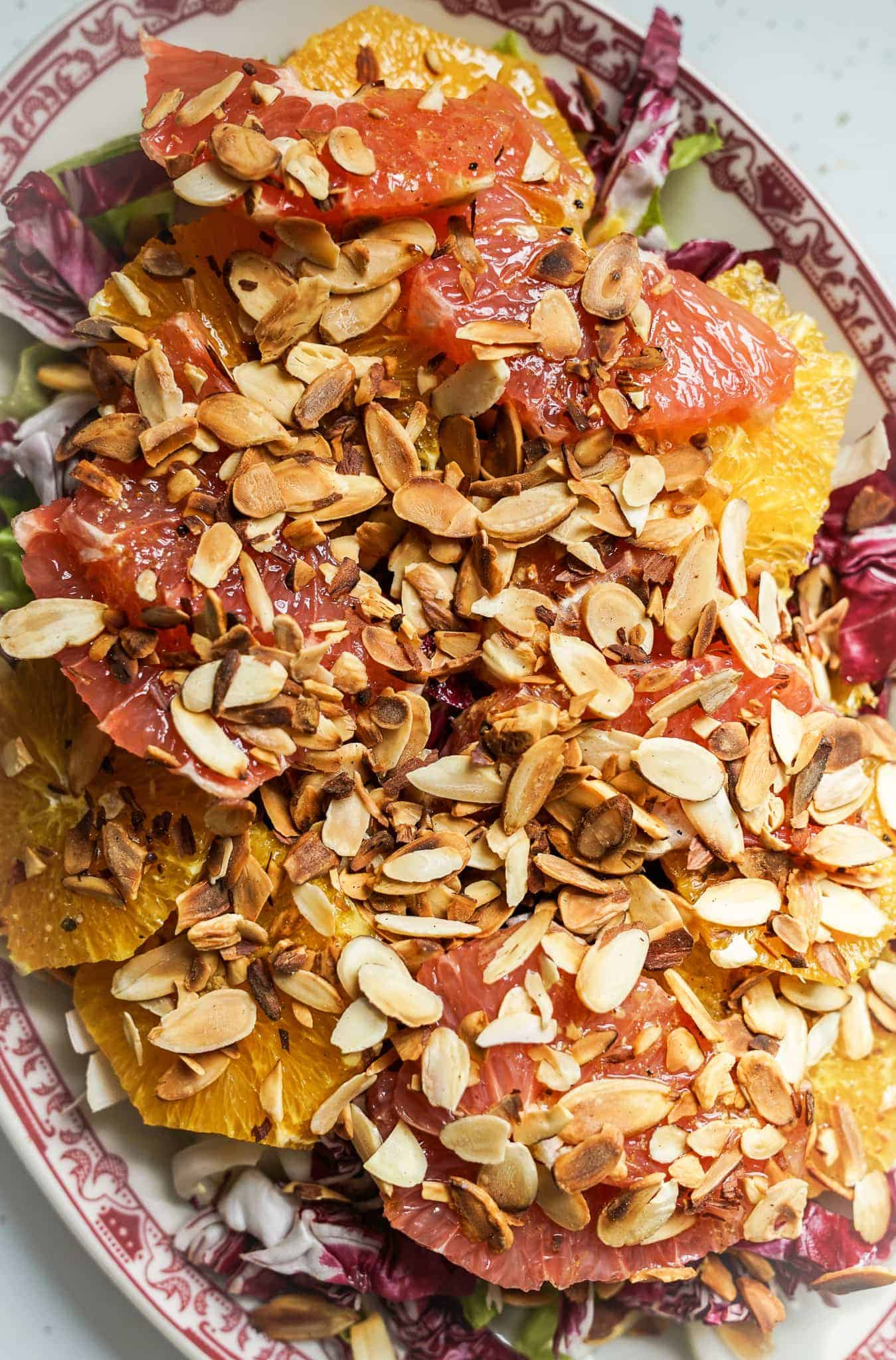 Oval platter of endive radicchio salad with oranges, grapefruit, and almonds