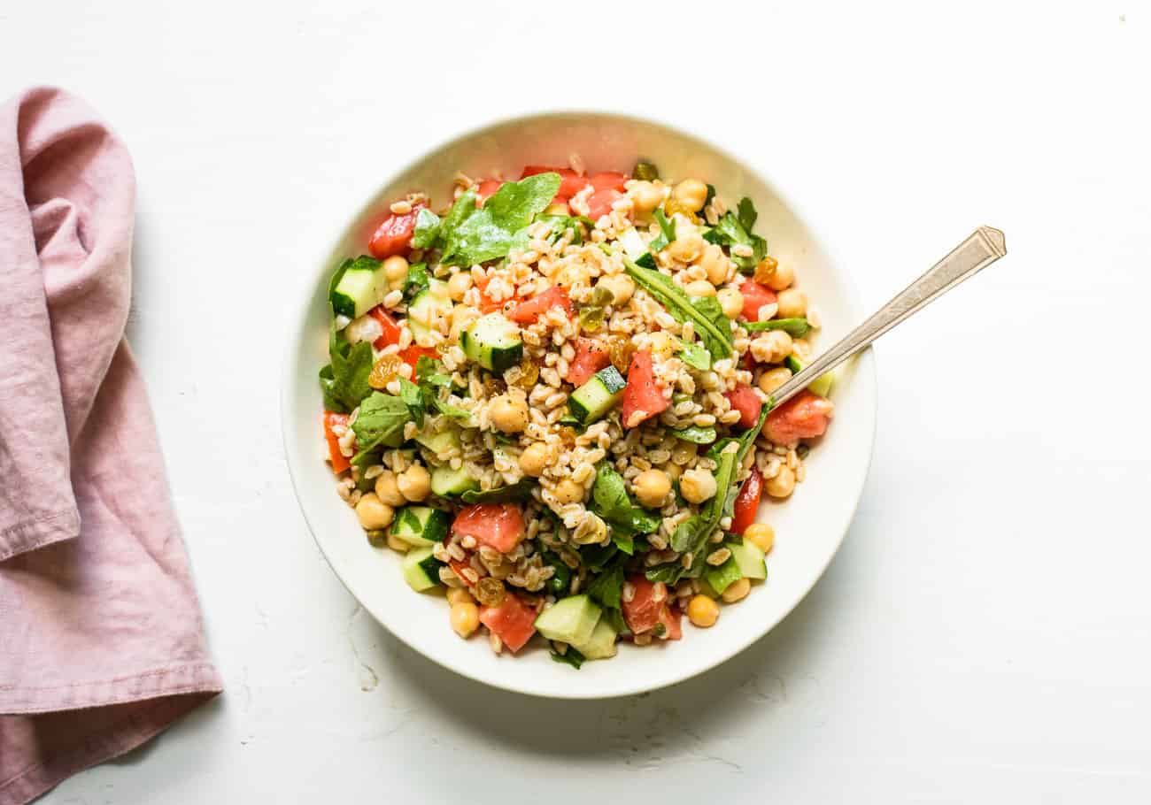 Summer farro salad in a white bowl on a white table next to a pink napkin