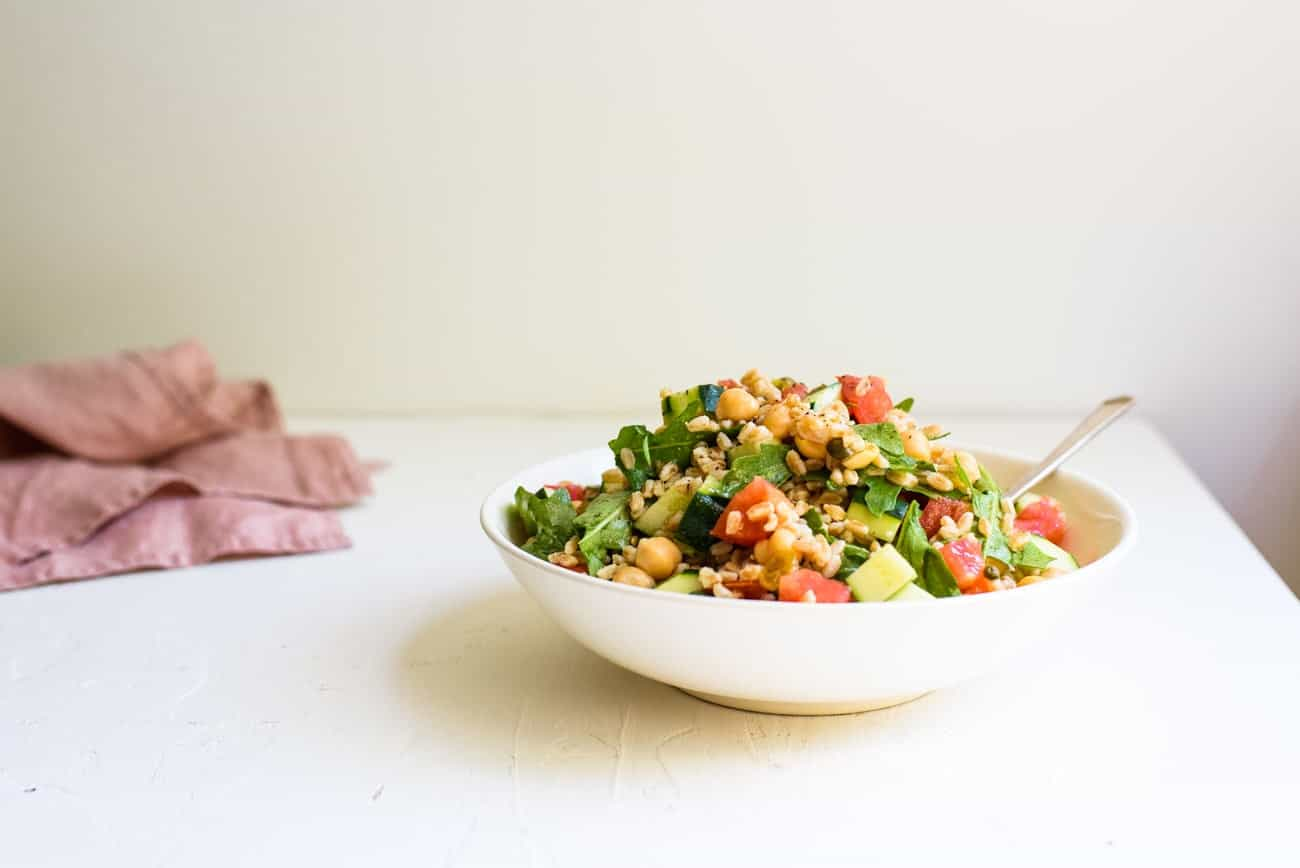 Summer farro salad in a white bowl on a white table