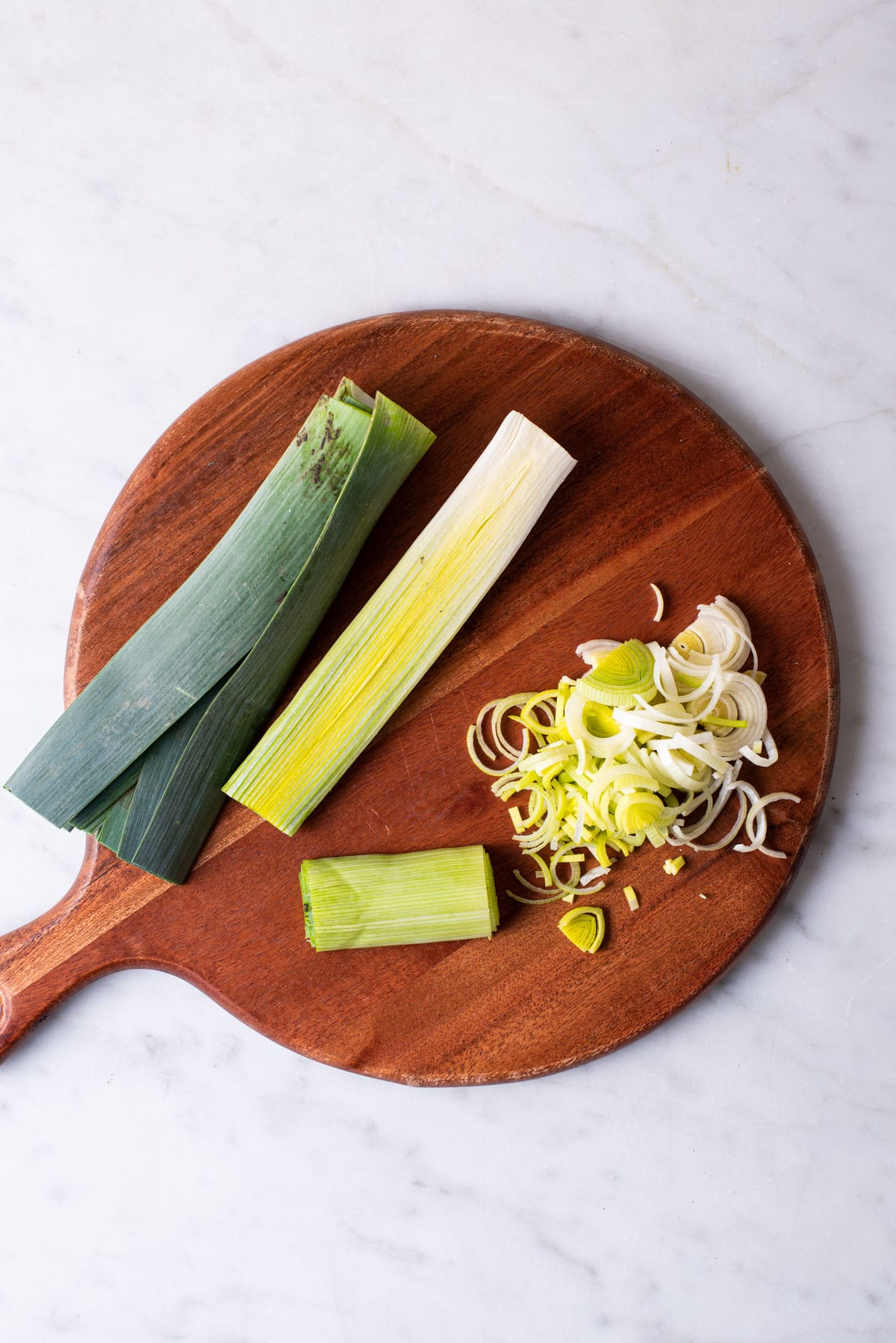 Three leeks on a wooden cutting board