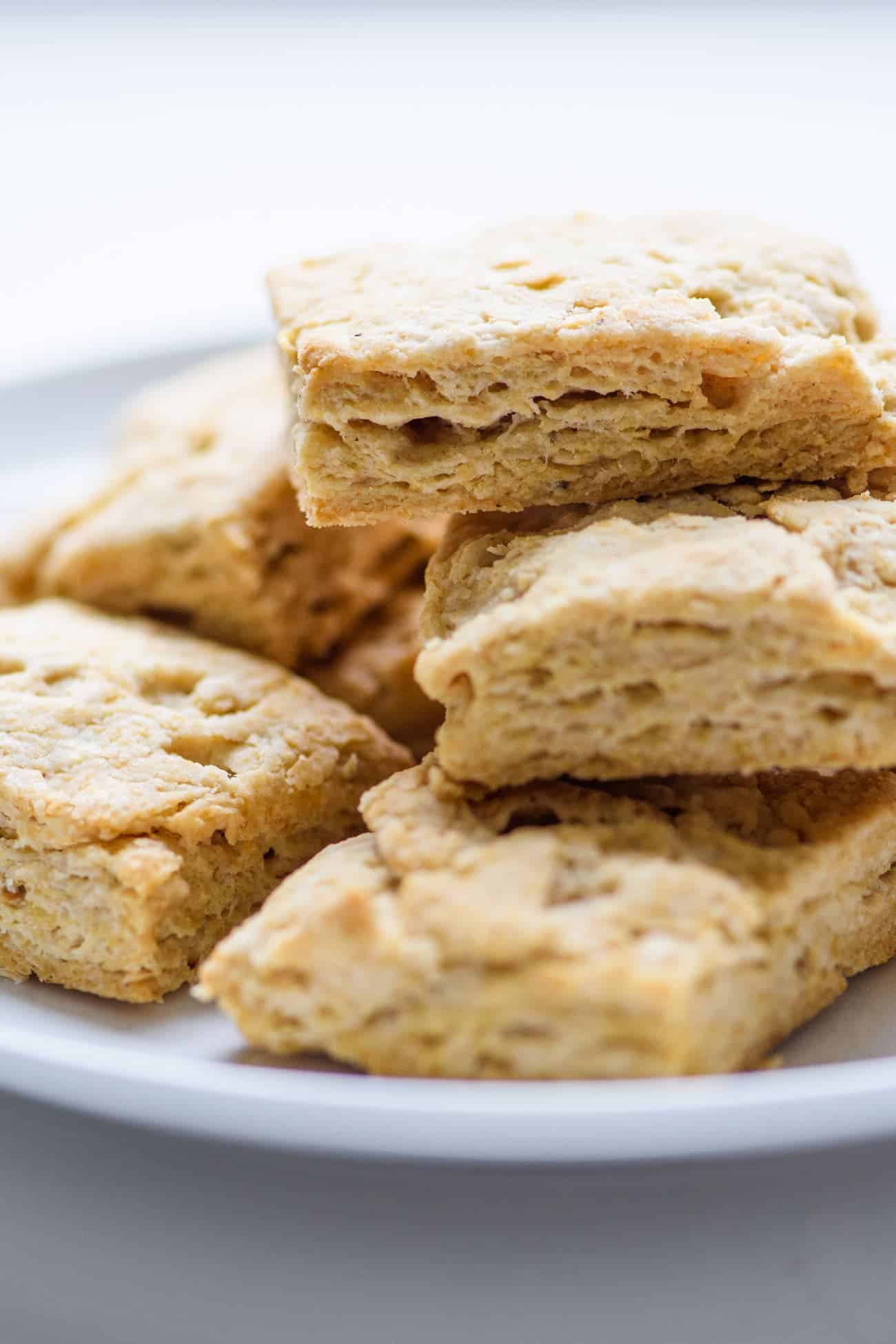 Vegan coconut oil biscuits stacked on a white plate