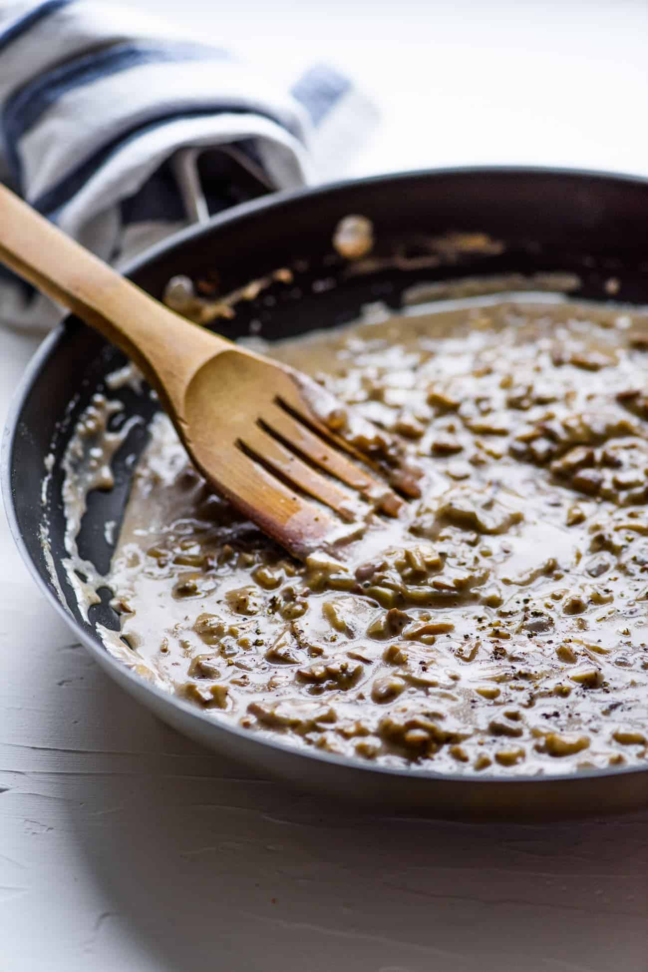 Creamy mushroom gravy in a skillet with a wooden spatula