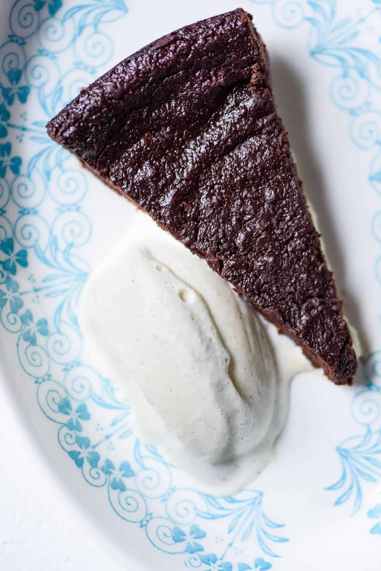 Slice of flourless chocolate cake with scoop of vanilla ice cream