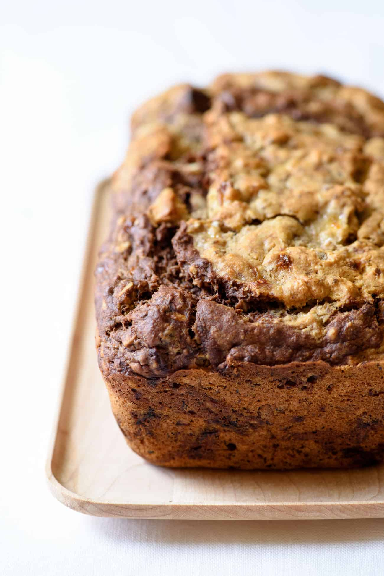 Marble banana bread loaf on a rectangular wooden plate on a while tablecloth