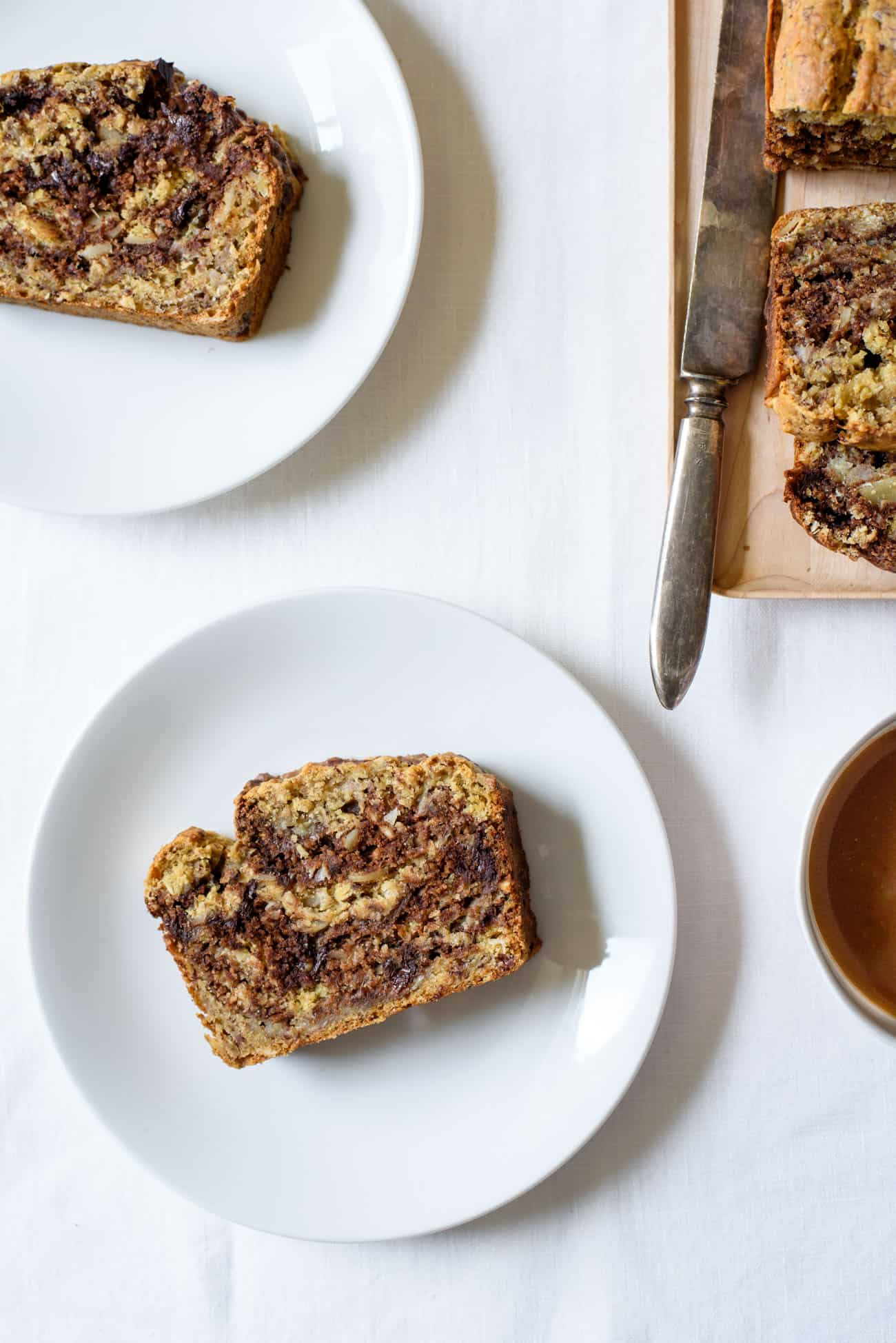 2 slices of marble banana bread on while plates on while tablecloth next to cup of coffee