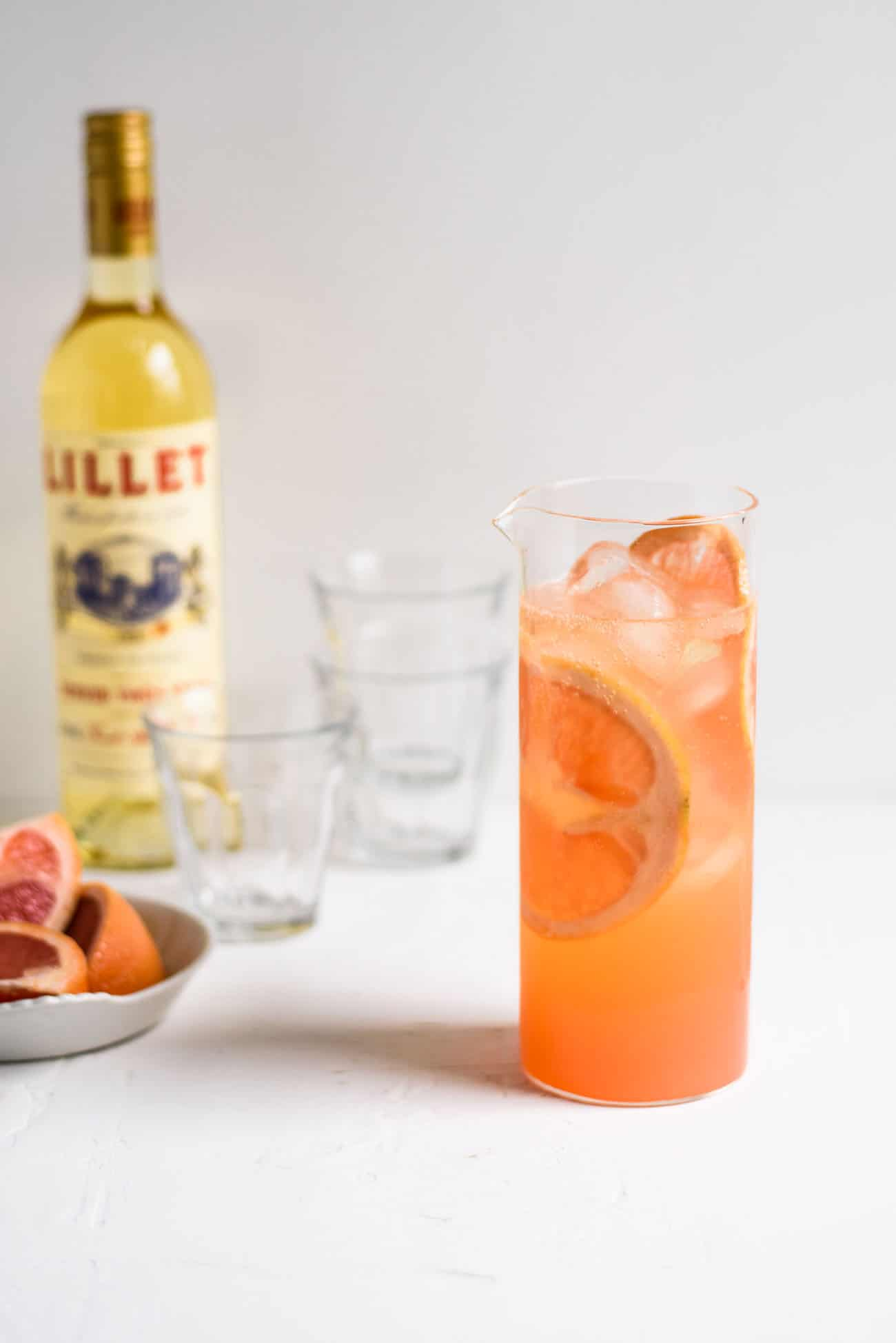 Grapefruit-Lillet Spritzer in a glass pitcher next to bottle of Lillet and grapefruit slices