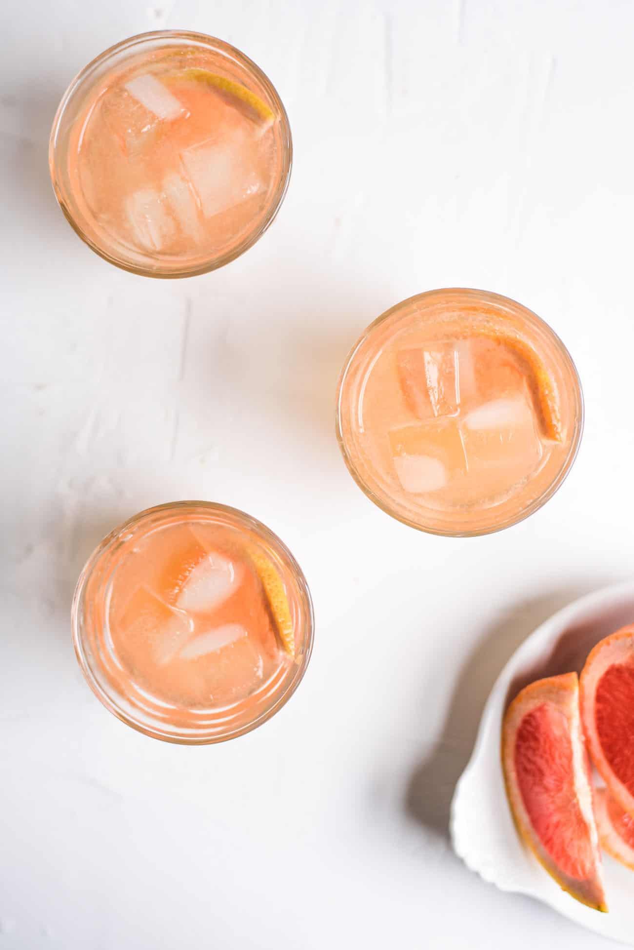 3 glasses of Grapefruit-Lillet Spritzer on white table