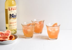 3 glasses of Grapefruit-Lillet Spritzer on white table