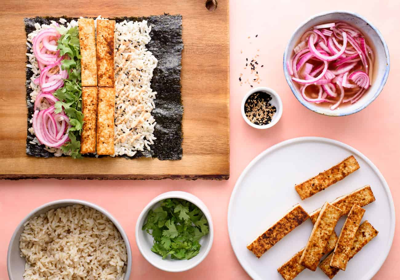 Assembly of sushi burrito recipe with nori on wooden cutting board surrounded by fillings in bowls