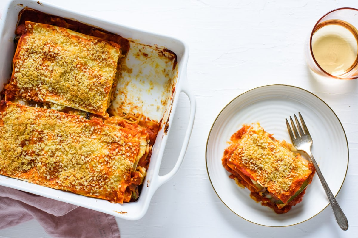Vegan vegetable lasagna in a square baking dish next to a plate with a slice of lasagna