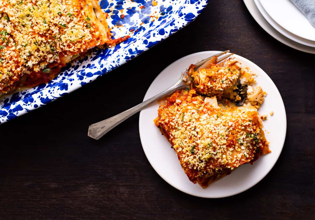 A slice of veggie lasagna on a white plate on a dark wooden table