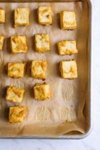 """Baked cubes of vegan tofu """"feta"""" on a baking sheet"""