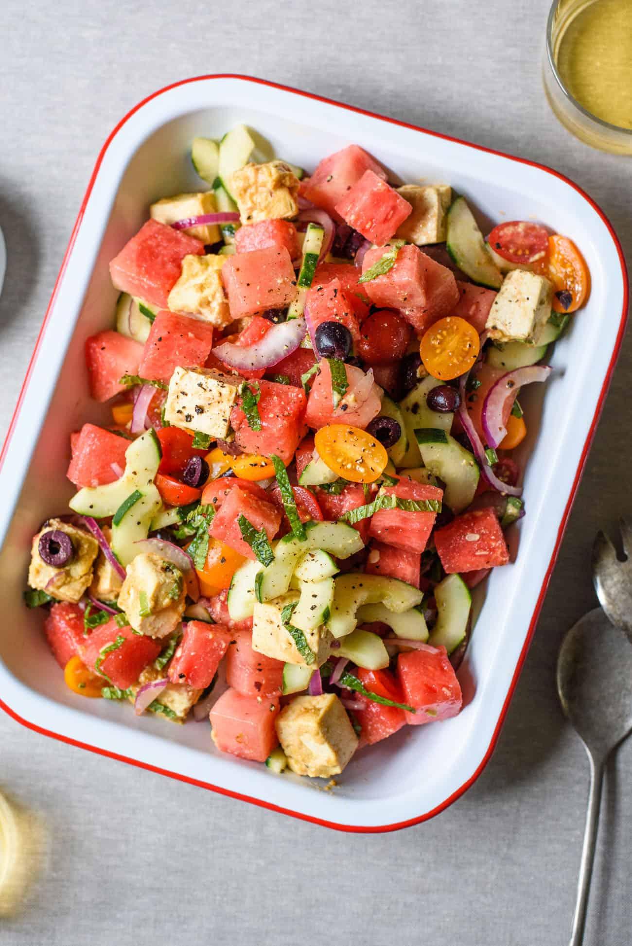 "Greek Watermelon Salad with Vegan Tofu ""Feta"" in a rectangular enamel dish"