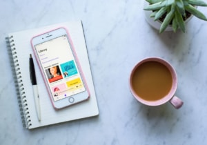 An iPhone on a notebook with the podcast app open next to coffee