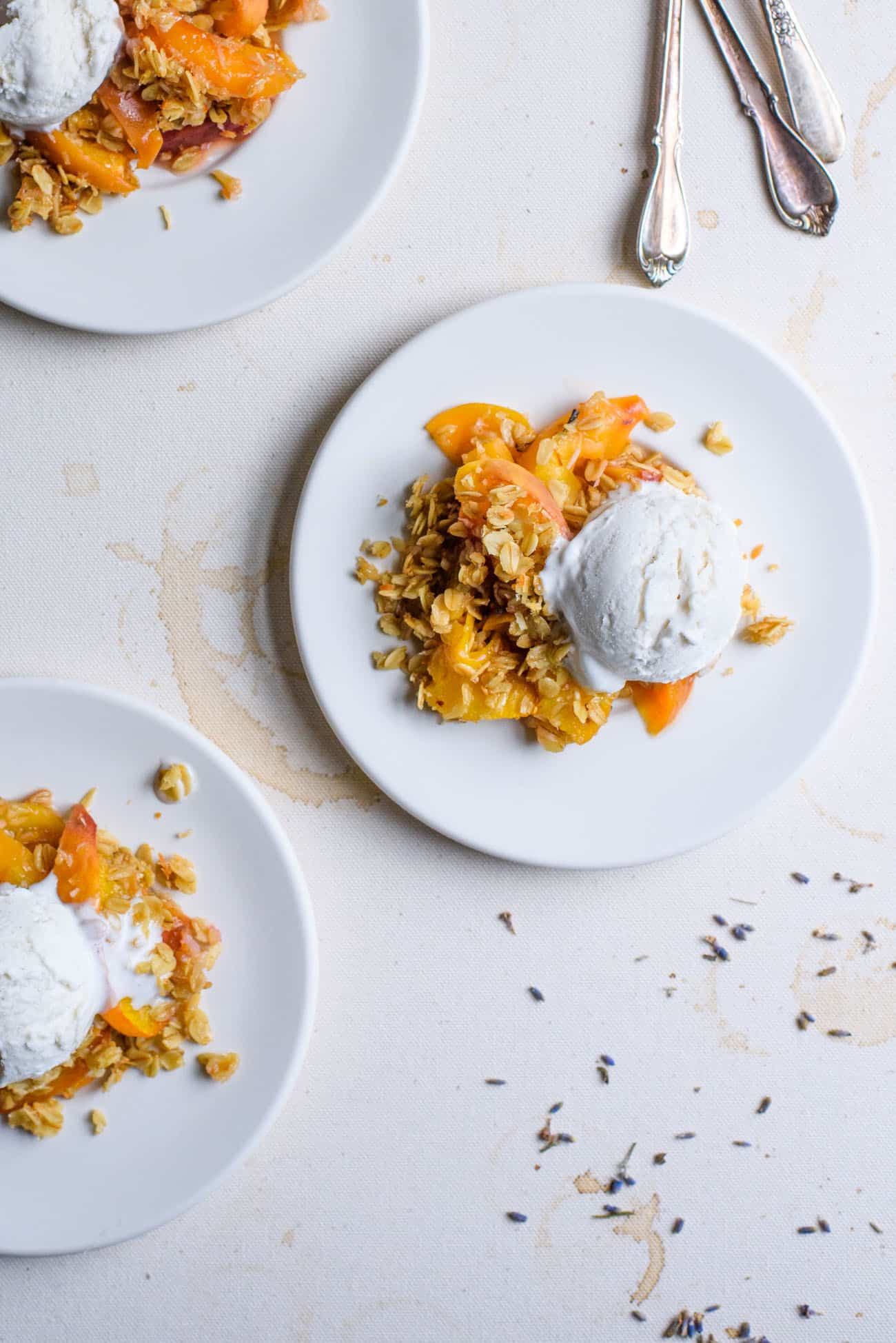 Three white plates with peach crisp with oats topped with vanilla ice cream