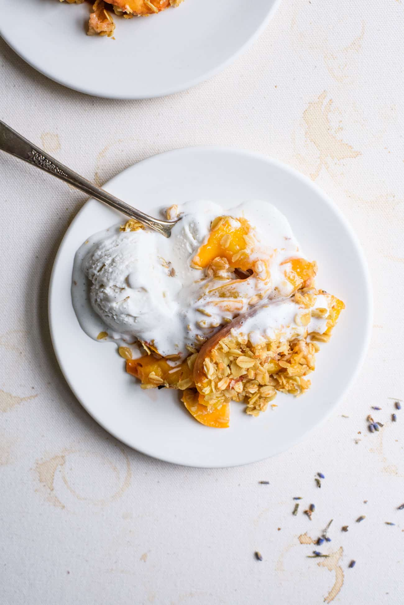 Peach crisp with oats on a white plate, topped with melting vanilla ice cream