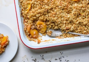 Enamel baking dish featuring a peach crisp with oats, next to scattered lavender flowers