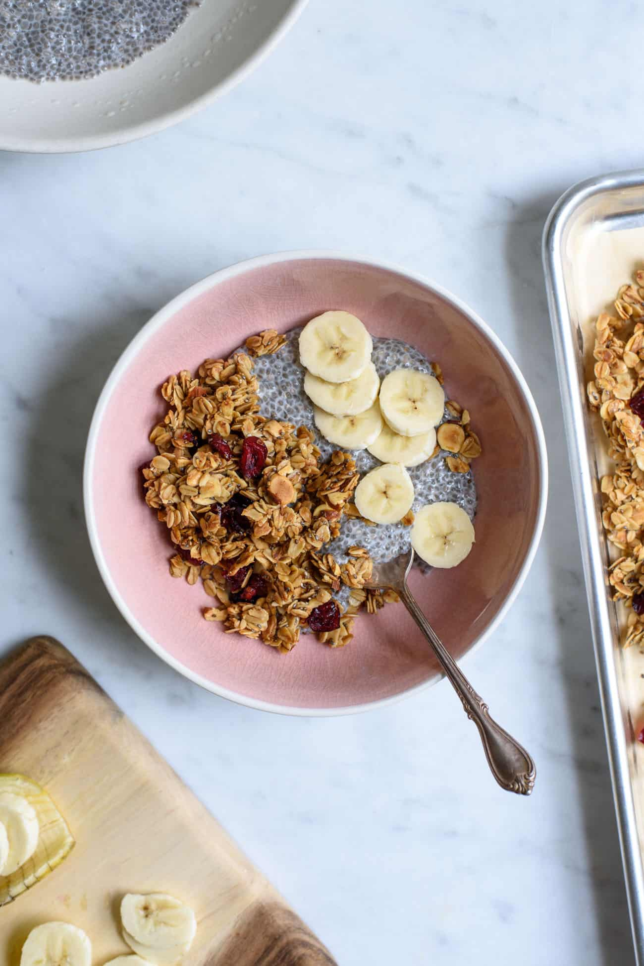 Pink bowl with chia pudding, granola, and bananas
