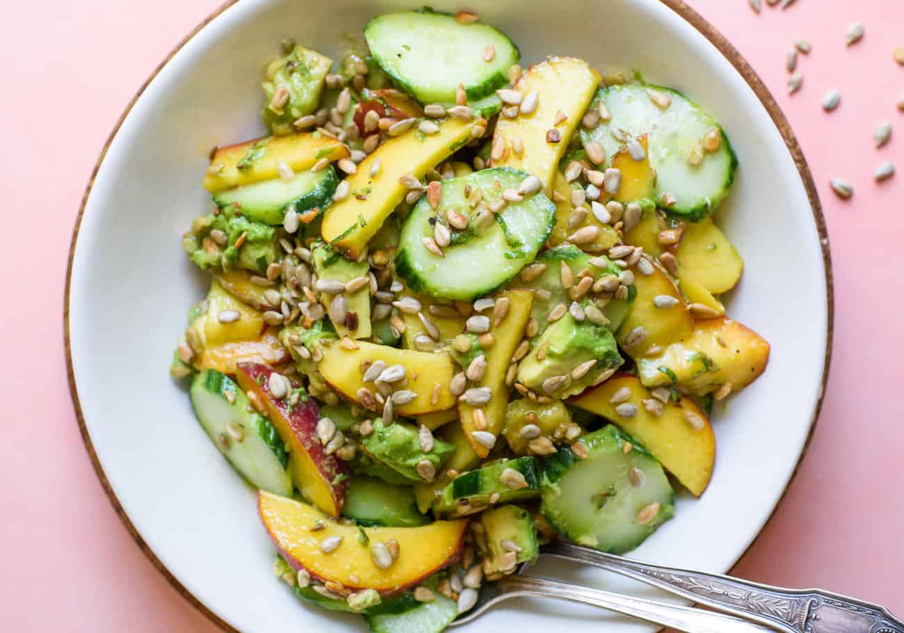 Close-up on white bowl of avocado peach salad with cucumbers and sunflower seeds
