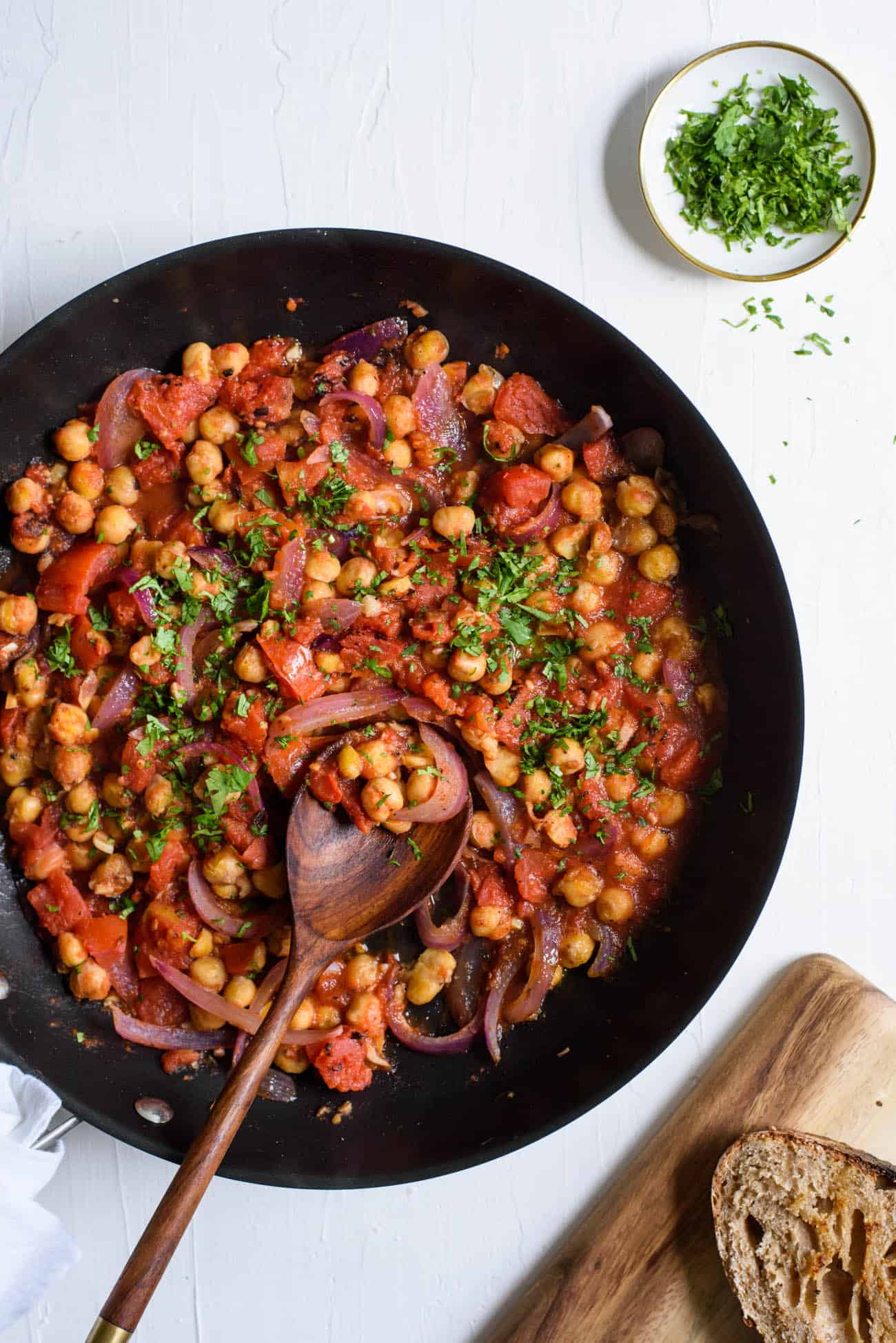 Curried chickpea breakfast hash in a skillet with a wooden spoon on a white table