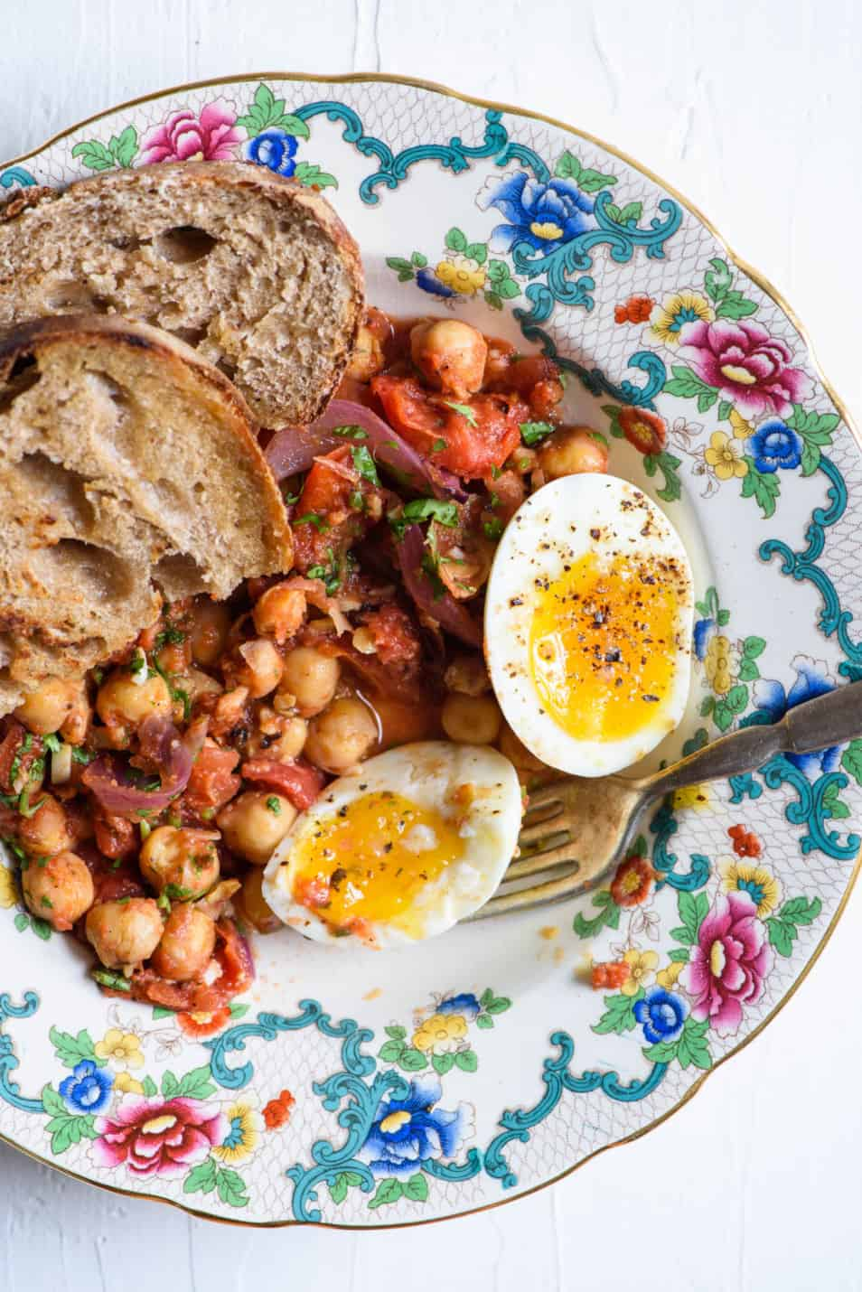 Curried chickpea breakfast hash on a colorful vintage plate with soft-boiled eggs and sourdough toast