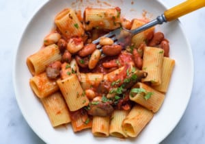 Close-up of tomato pasta with beans and mushrooms in a white bowl