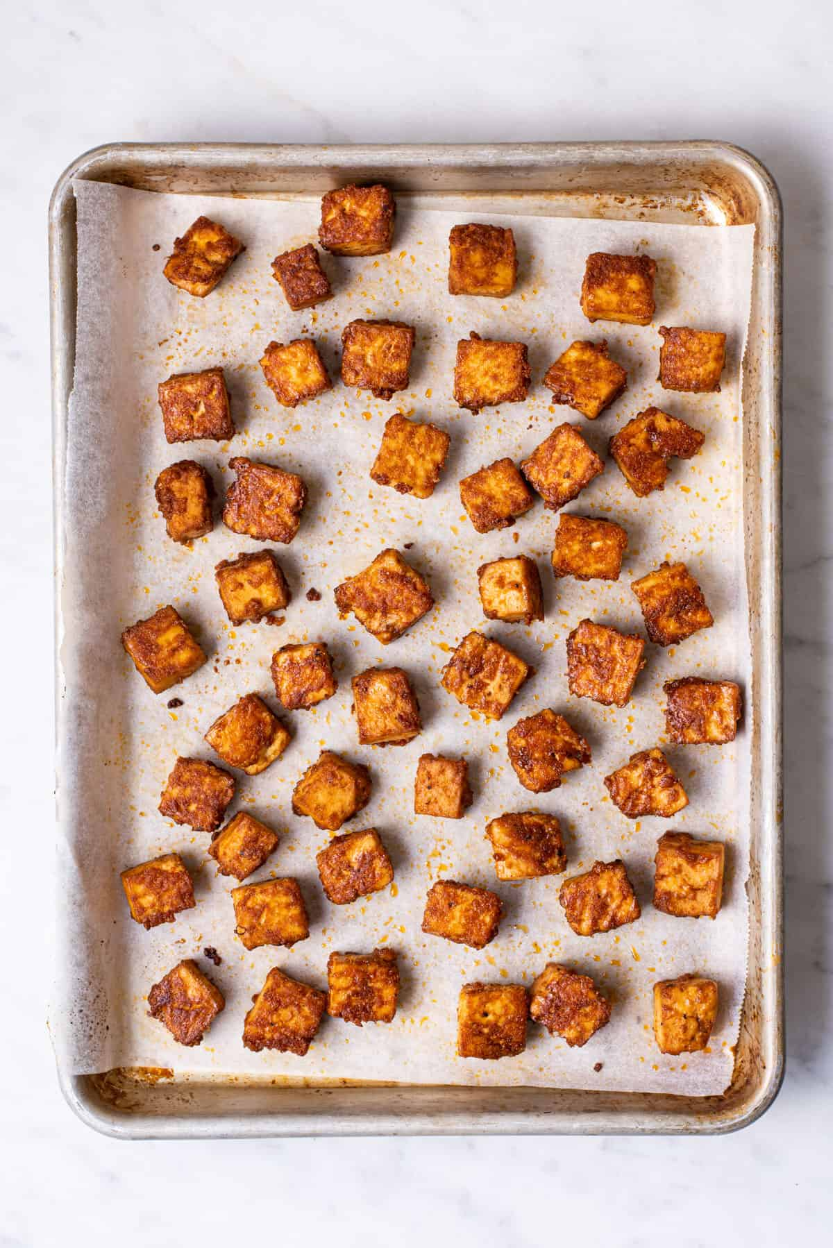Cubes of baked tofu on a parchment-covered baking sheet