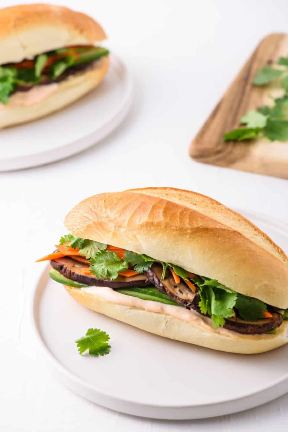 2 vegetarian banh mi sandwiches with portobello mushrooms and pickled carrots on white plates with a wooden cutting board in the background