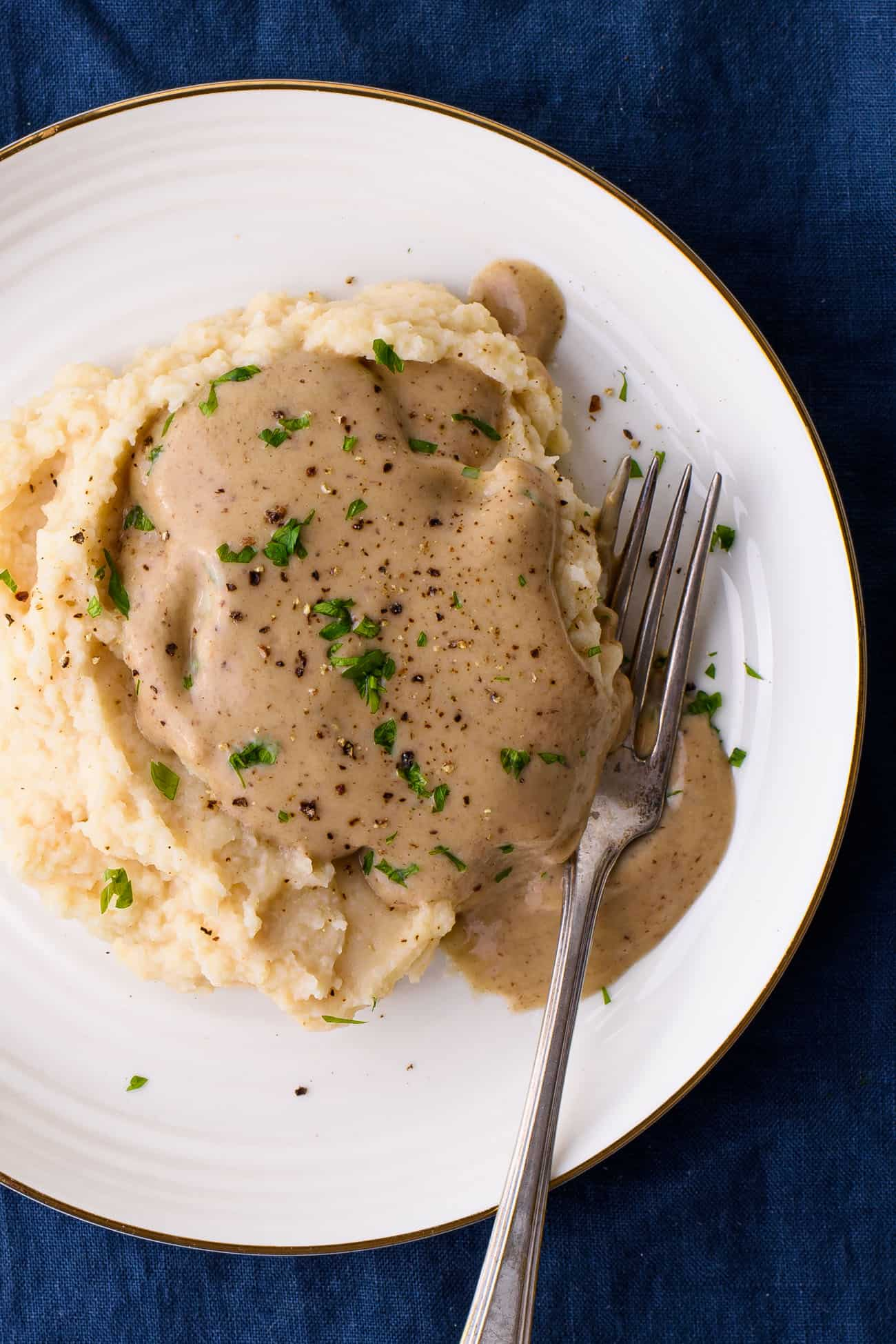 Close-up of vegan mushroom gravy on celeriac puree with minced parsley
