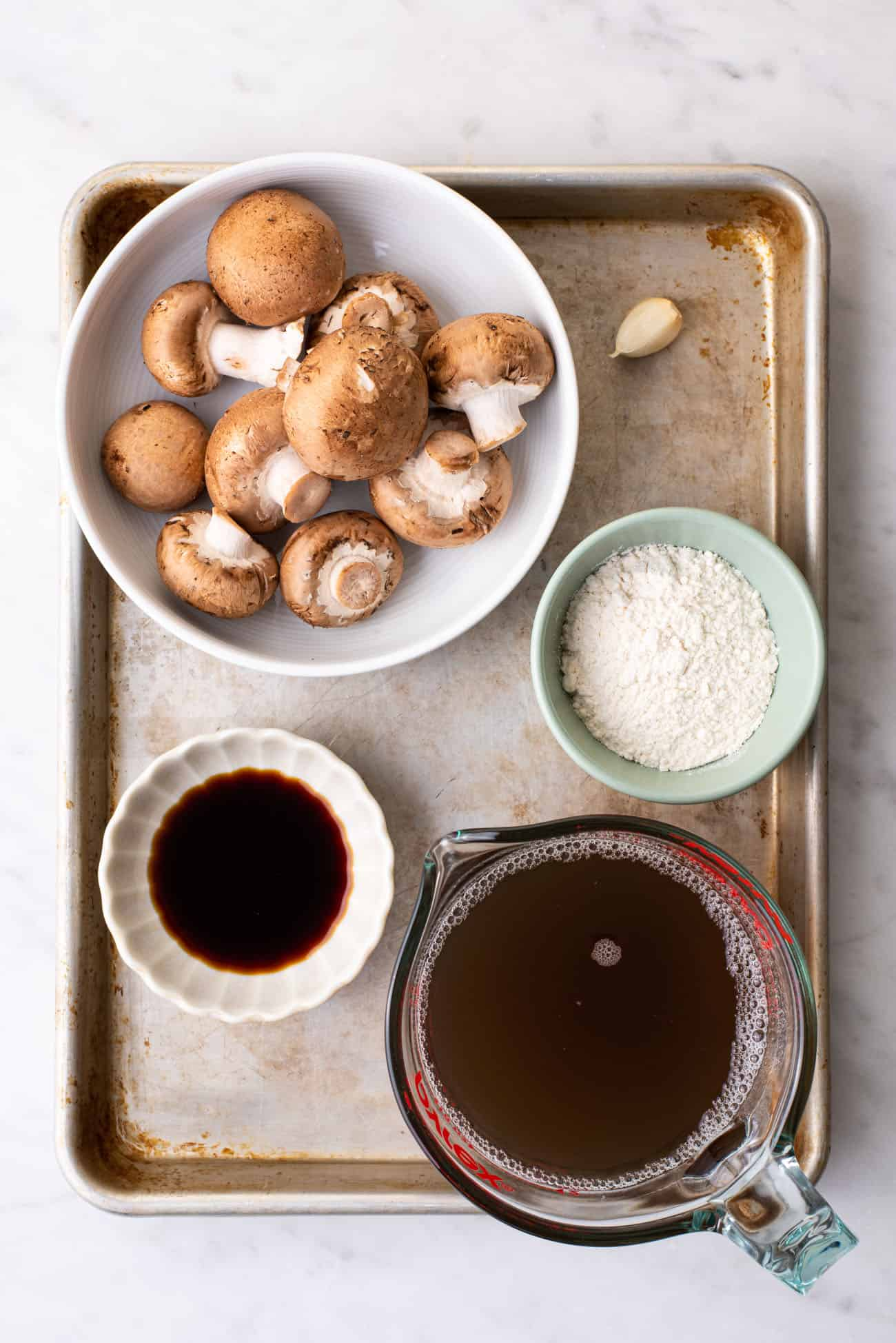 Ingredients to make vegan mushroom gravy laid out on marble table: mushrooms, flour, soy sauce, and broth