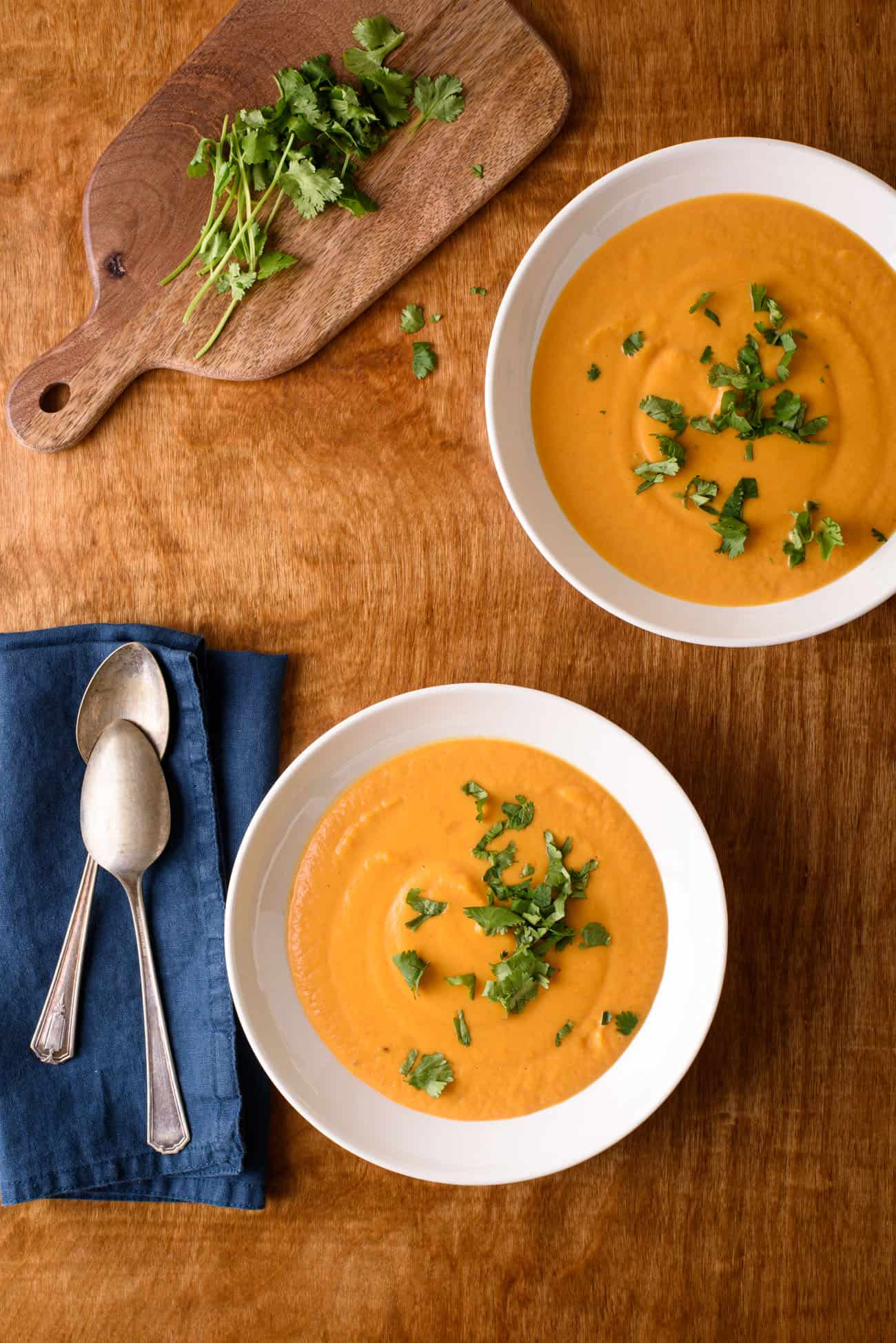 Two bowls of curried butternut squash soup with cilantro on a wooden table