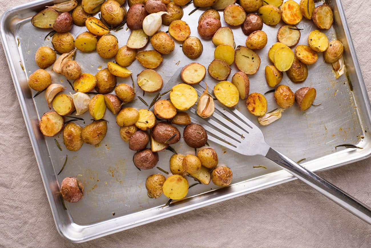 Garlic rosemary roasted potatoes on a baking sheet with a metal spatula