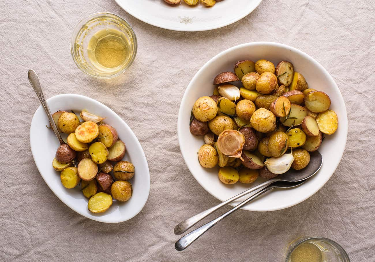 Bowl of garlic rosemary roasted potatoes on beige tablecloth