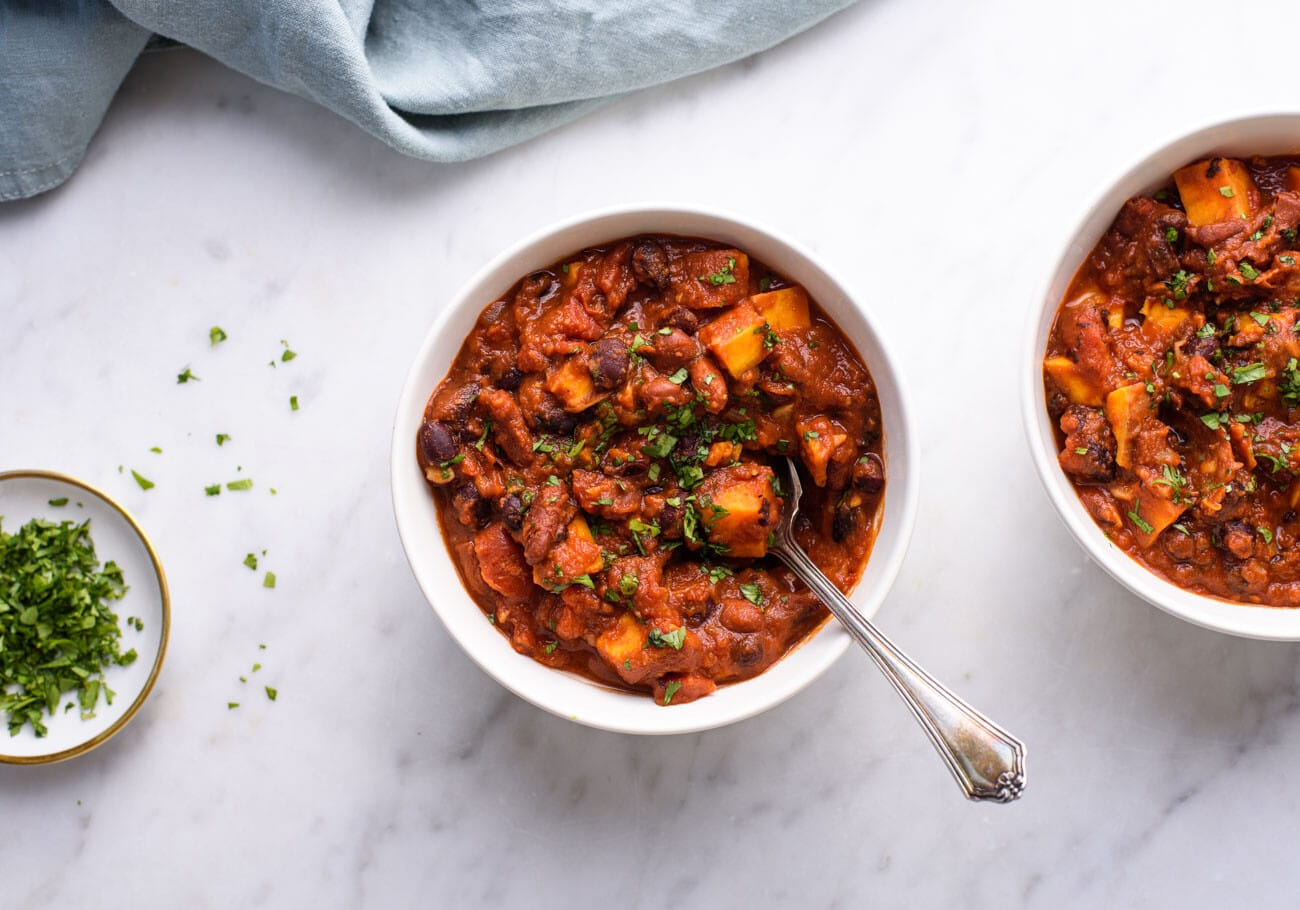 Two bowls of vegetarian bean chili on a marble table