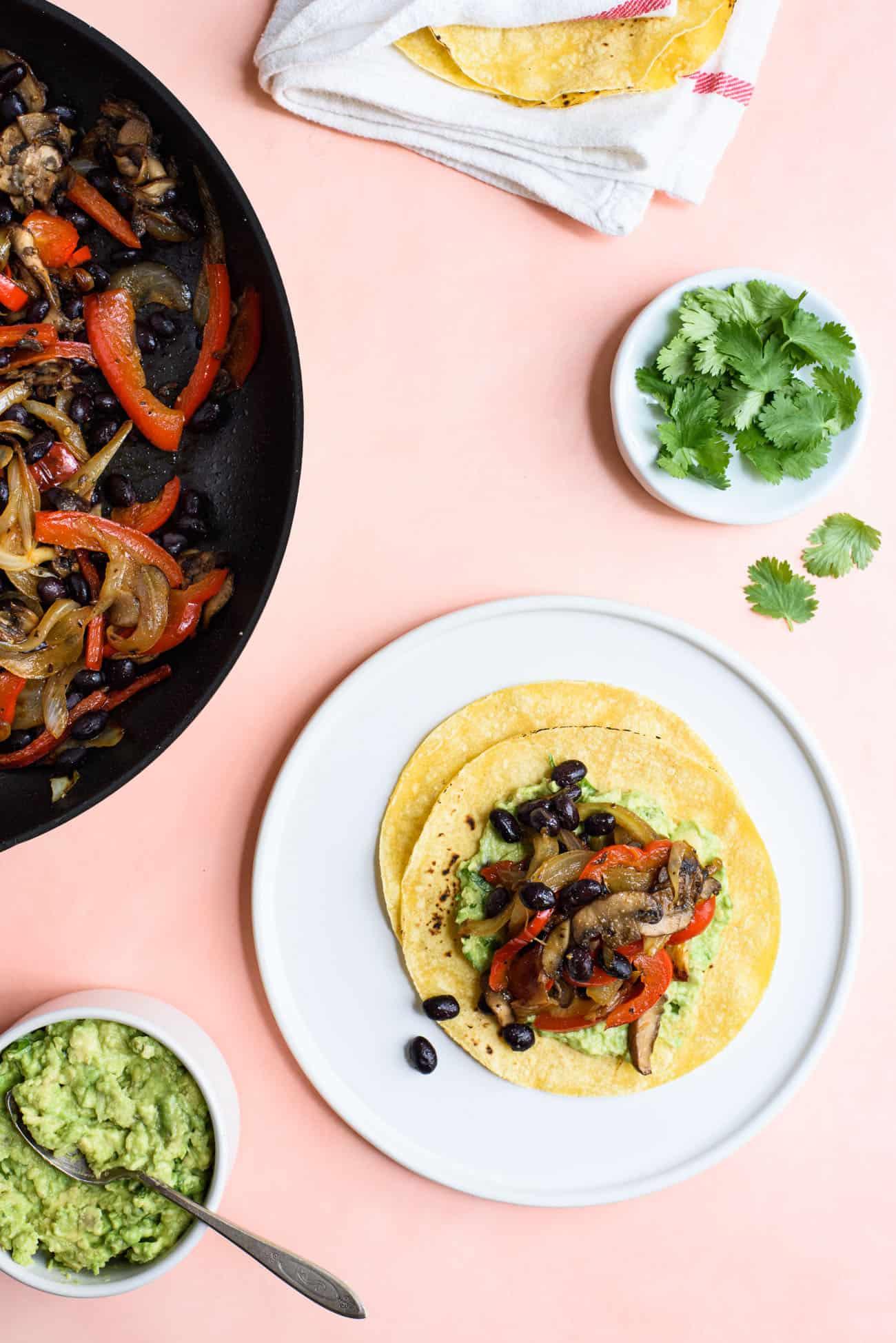 Vegan tacos on a white plate next to a skillet with fajita veggies