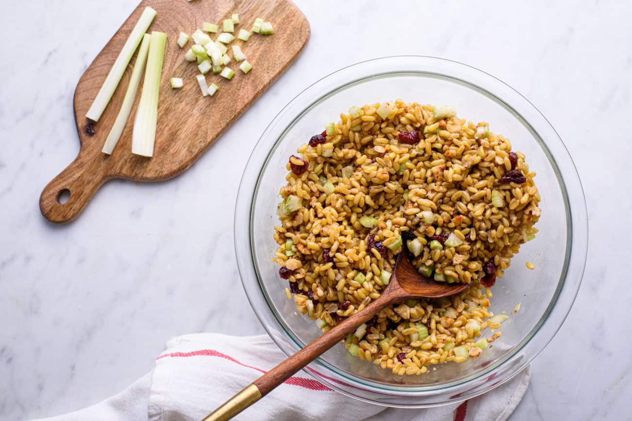 Glass Pyrex bowl of wheatberry salad with celery, cranberries, and walnuts